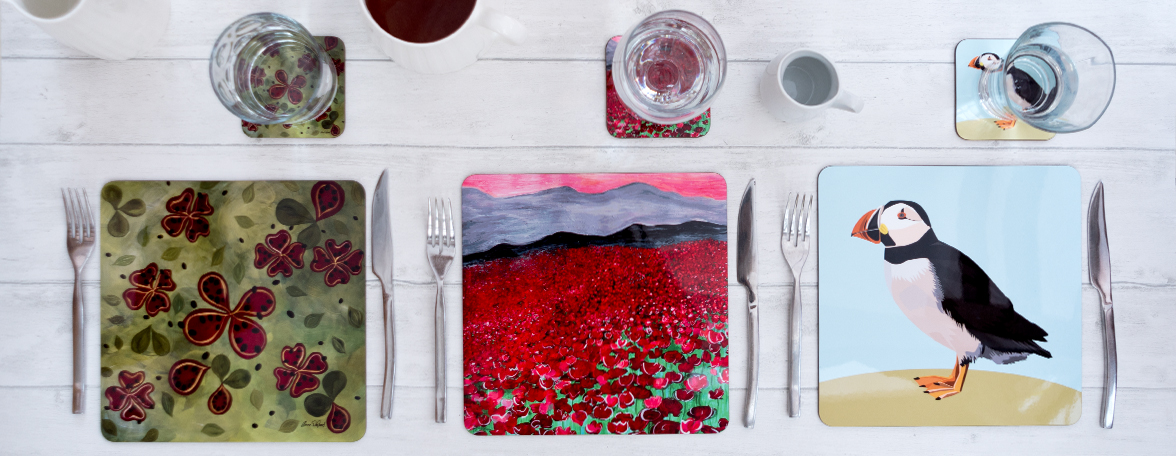 Three table settings with three high gloss placemat designs and their matching coasters. The designs from left to right are Peanut butter fruits, Poppies and Percy Puffin.